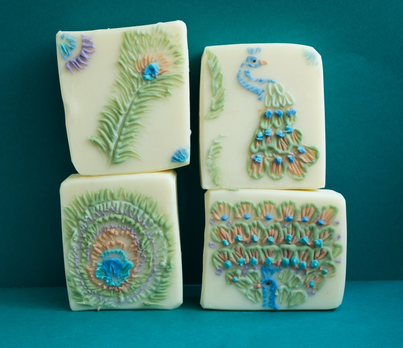 Set of four white soaps featuring a peacock them through thin piped lines